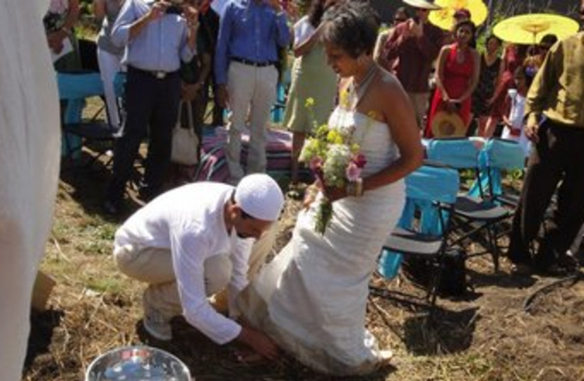 The groom washes the feet of his bride during the wedding (photo credit: Micha'el BedarShah/JTA)