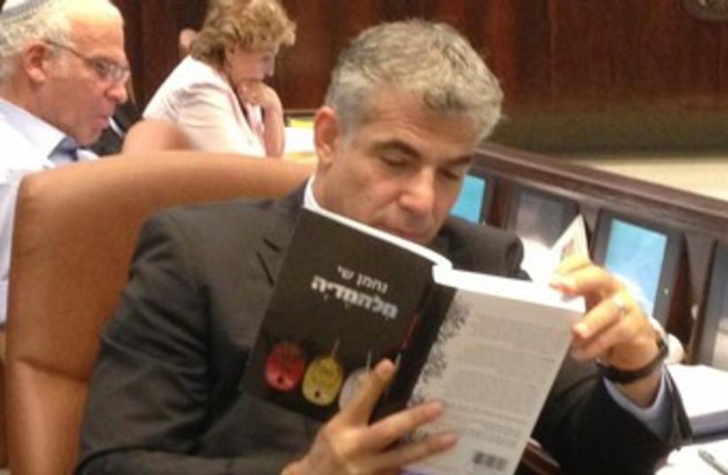 Finance Minister Yair Lapid reading 370 (photo credit: Noa Amir )