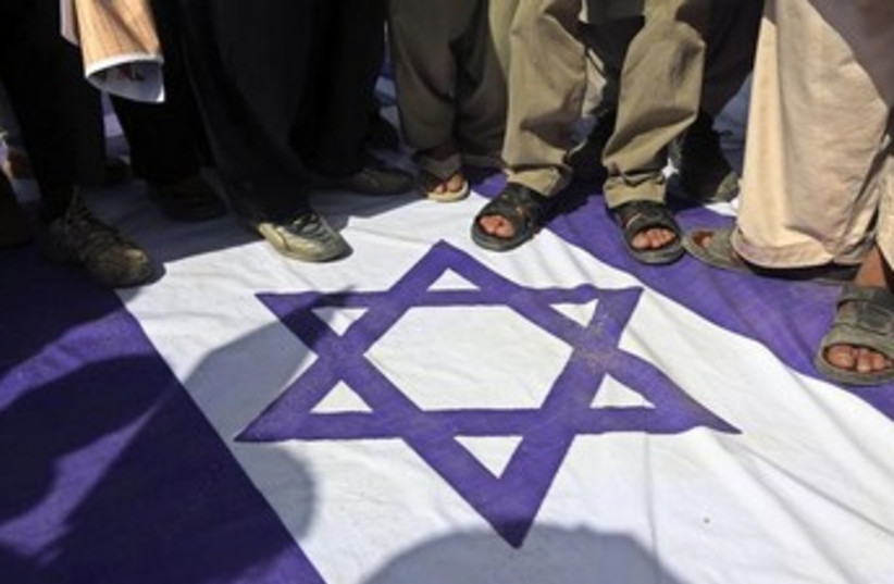 Stepping on Israeli flag 370 (photo credit: REUTERS/Omar Sobhani )