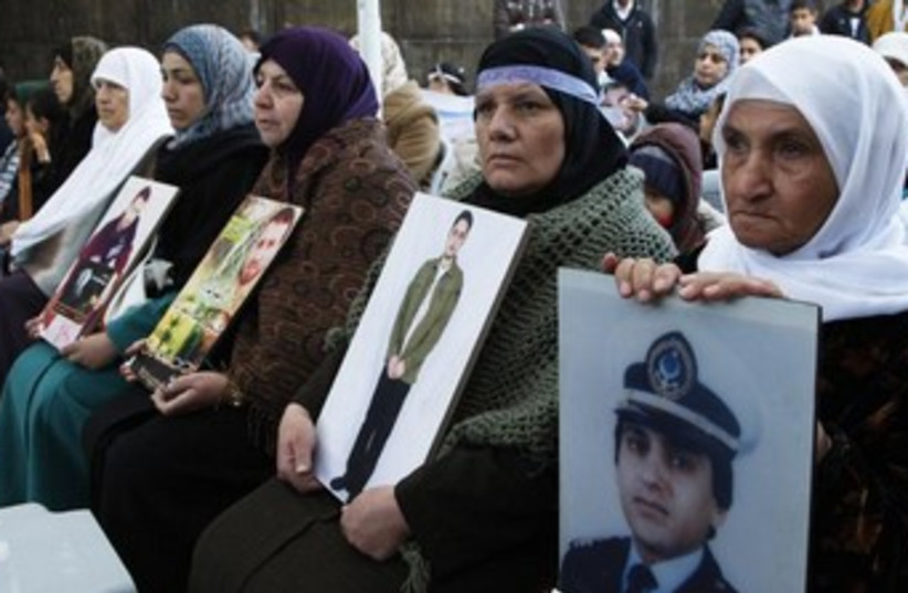 Women hold up pictures of Palestinian prisoners 370 (photo credit: REUTERS/Majed Jaber)