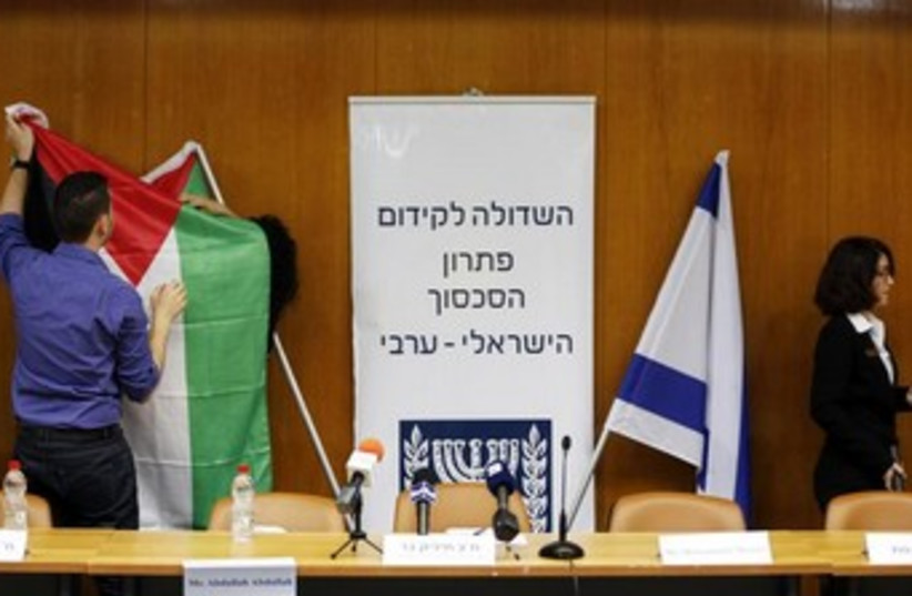 Israeli parliament employees set up a Palestinian flag  (photo credit: Reuters)