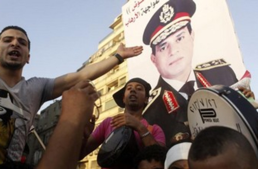 Anti-Morsi protesters hold up Sisi poster 370 (photo credit: REUTERS)