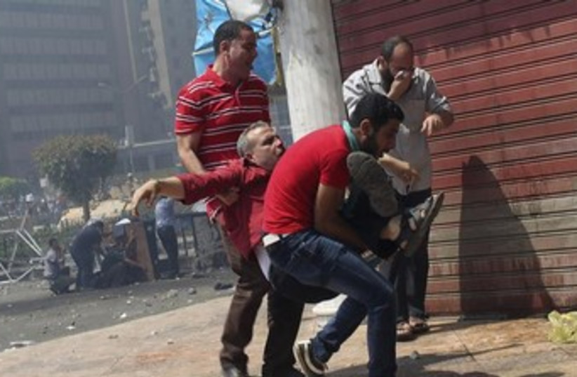 Protesters carry injured man in Cairo 370 (photo credit: REUTERS)