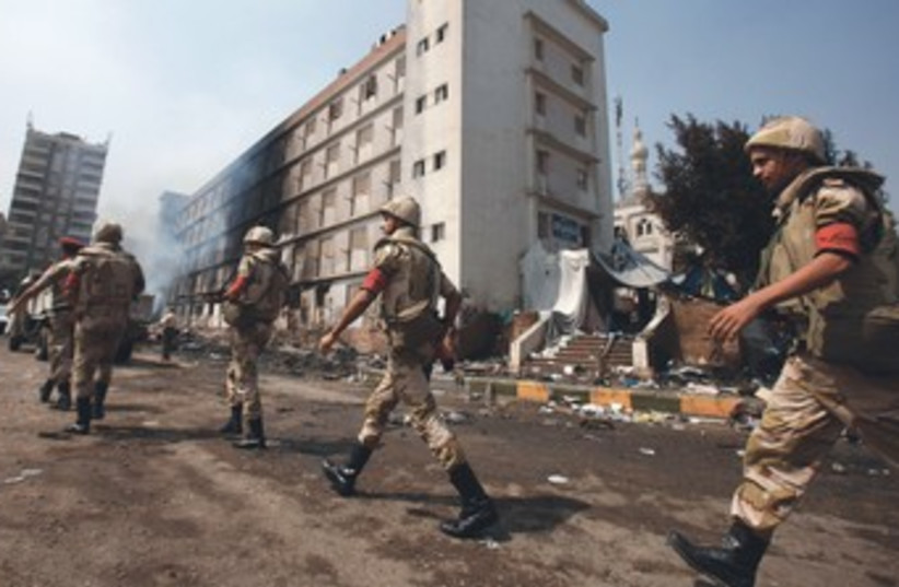 Egypt soldiers walk passed burnt building 370 (photo credit: REUTERS)