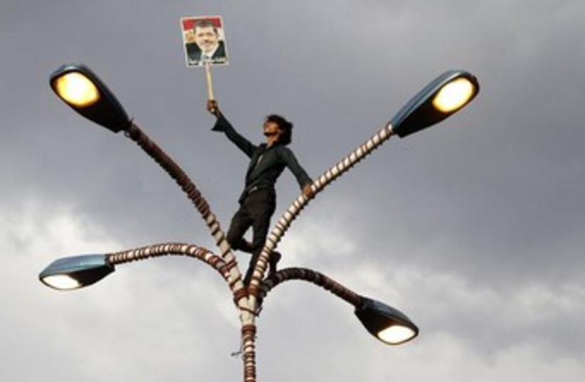 Morsi supporter on street lamp 370 (photo credit: REUTERS)
