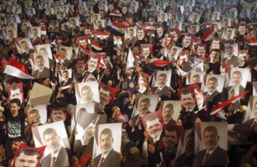Morsi supports hold posters in Cairo 370 (photo credit: REUTERS)