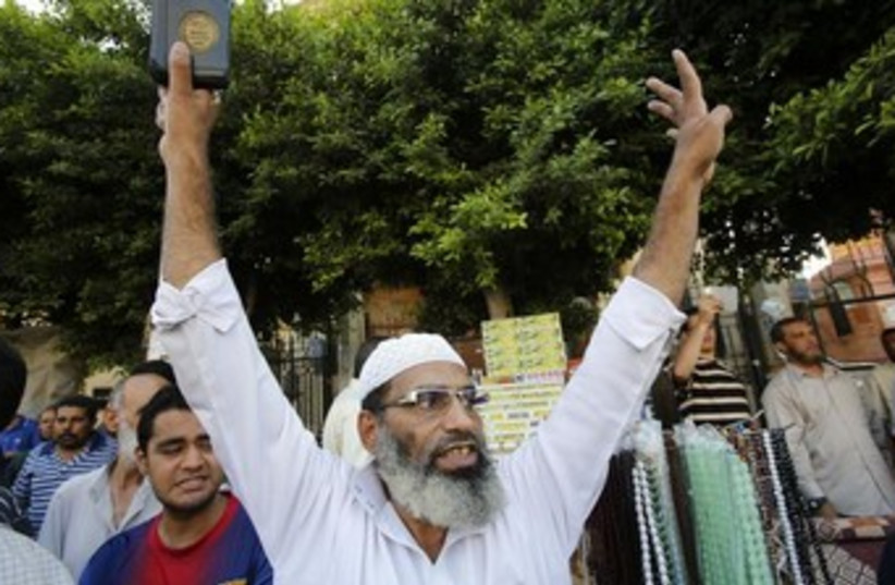 Muslim protester raises arms 370 (photo credit: REUTERS)