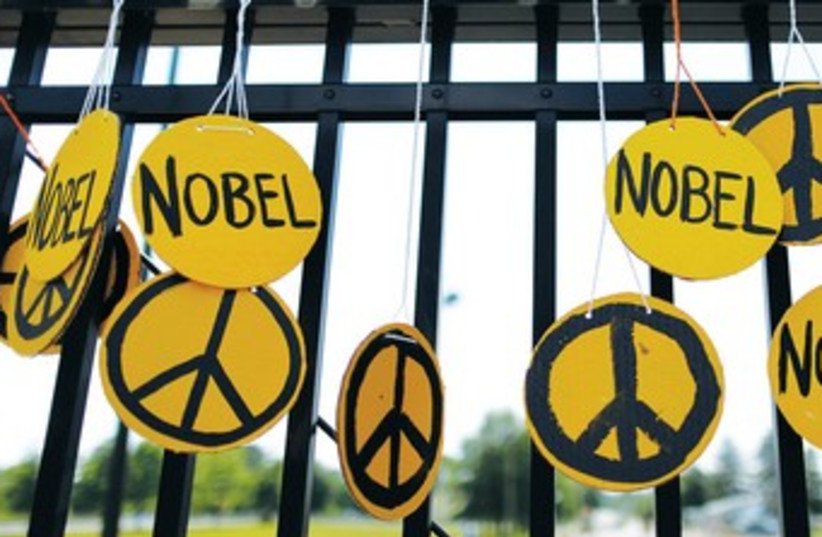PEACE SYMBOLS adorn a fence. 370 (photo credit: REUTERS)