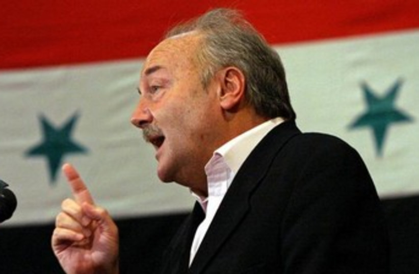 George Galloway with Syria flag (photo credit: REUTERS/Bassam Khabieh)