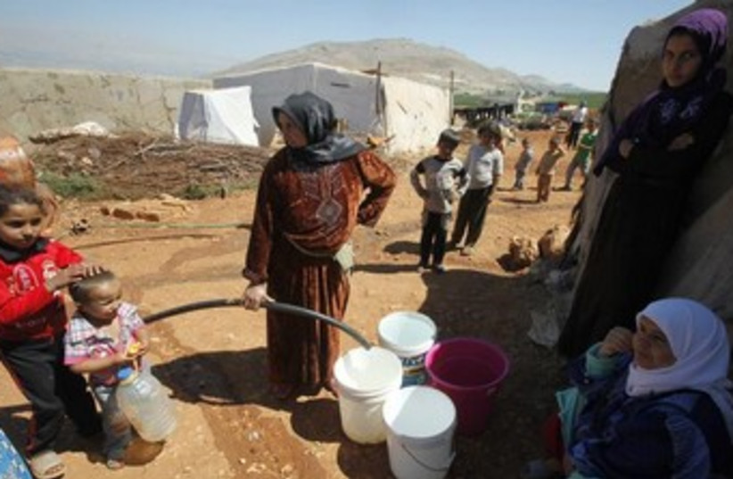 Syrian refugees fill buckets with water 370 (photo credit: REUTERS)