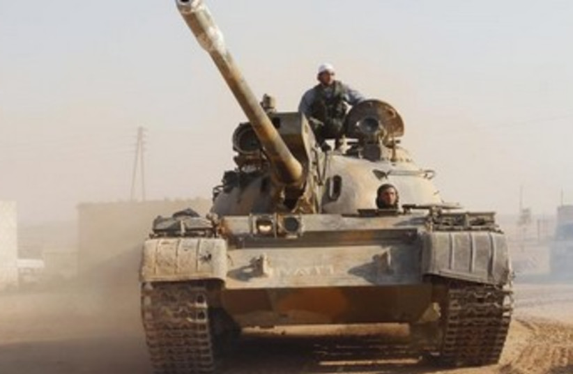 Free Syrian Army fighter drives a tank 370 (photo credit: Reuters)