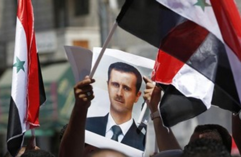 Protester holds a poster of Syria's President Bashar Assad (photo credit: Reuters)