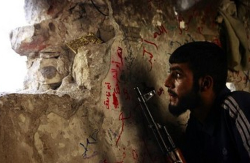 A Free Syrian Army fighter sits on a lookout  370 (photo credit: REUTERS)