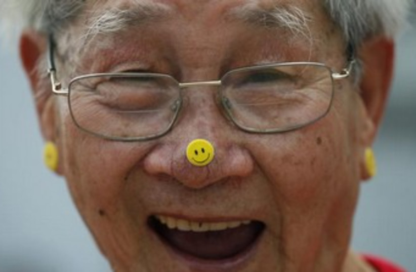 A man practices Laughter Yoga during the World Laughter Day (photo credit: Reuters)