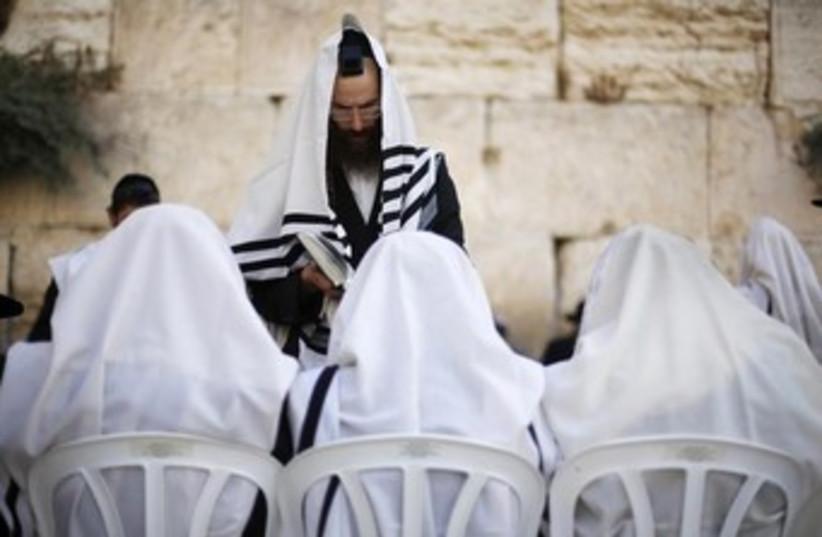 Jewish worshippers covered in prayer shawls pray @kotel 370 (photo credit: Courtesy Yazel Shavit Communications)
