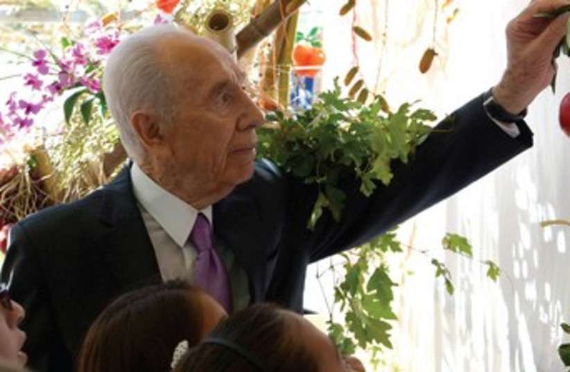 Shimon Peres decorating Succa370 (photo credit: Mark Neiman/GPO)