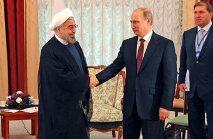 Putin and Rouhani shake hands 370 (photo credit: REUTERS)