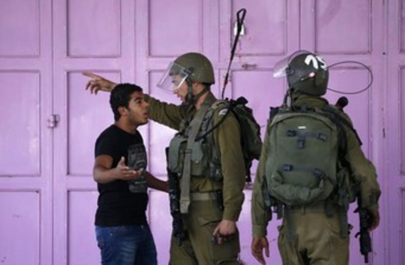 idf soldier and palestinian argue 370 (photo credit: REUTERS)
