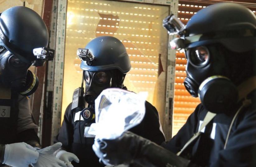 UN expert holds sampels from an alleged attack in Damascus. (photo credit: AMIR HASHEN DEHGANI / FARS NEWS / REUTERS)