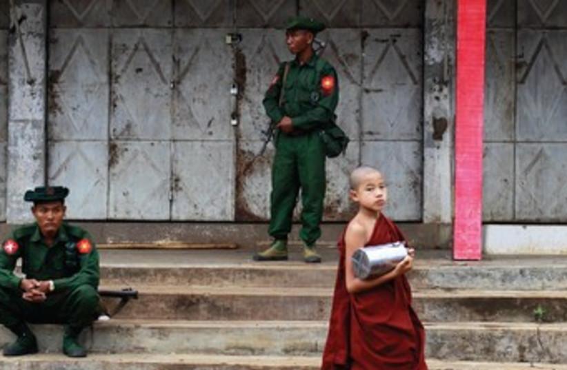 Buddhist monks walk apst soldier Myanmar 370 (photo credit: REUTERS)