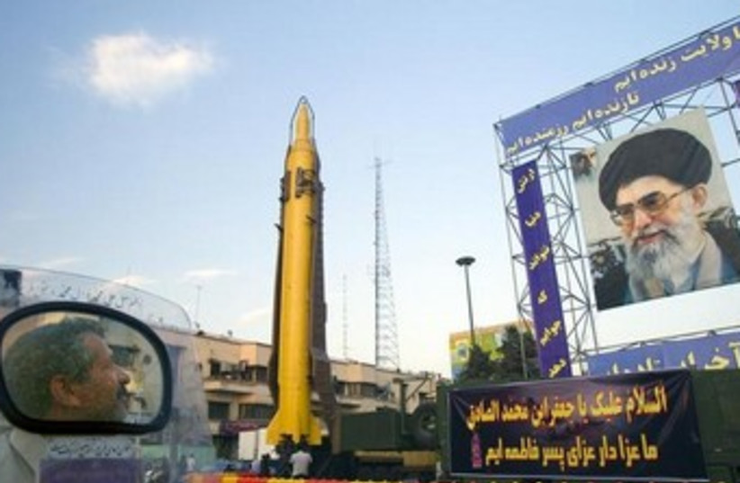 A motorcyclist looks at an Iranian-made Ghadr-F missile (photo credit: Reuters)