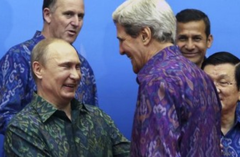 Russia's President Vladimir Putin shakes hands with Kerry (photo credit: Reuters)