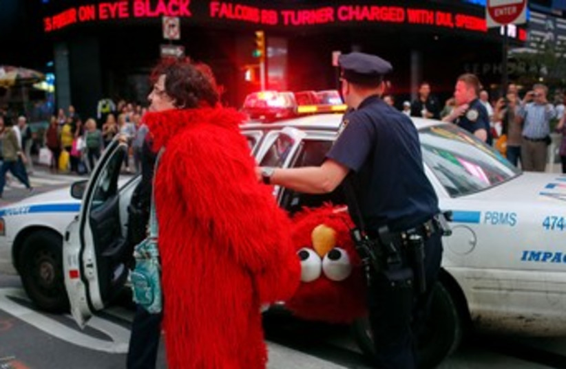 Dan Sandler, dressed as Elmo, is handcuffed and detained 370 (photo credit: reuters)