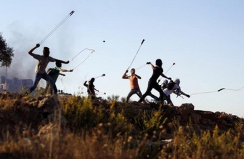 Palestinians hurl slingshots at IDF troops 370 (photo credit: REUTERS)