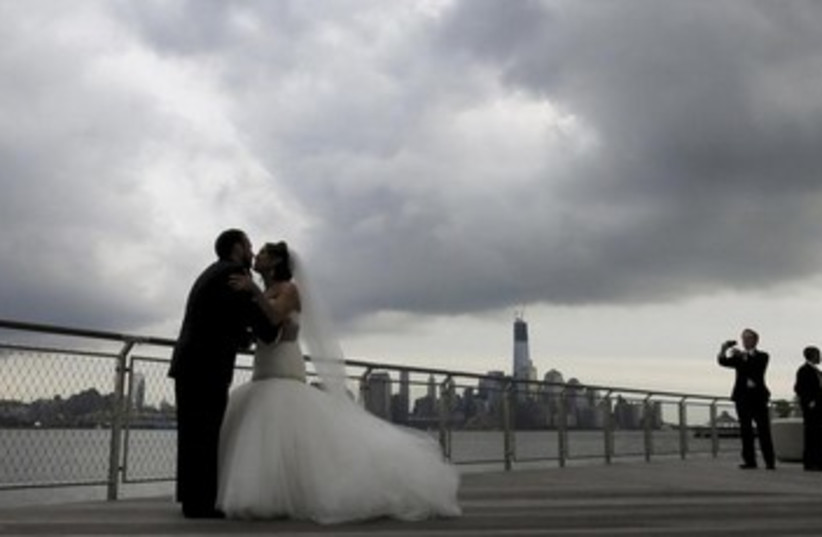 Bride and groom pose under rain clouds [illustrative] (photo credit: REUTERS/Gary Hershorn)