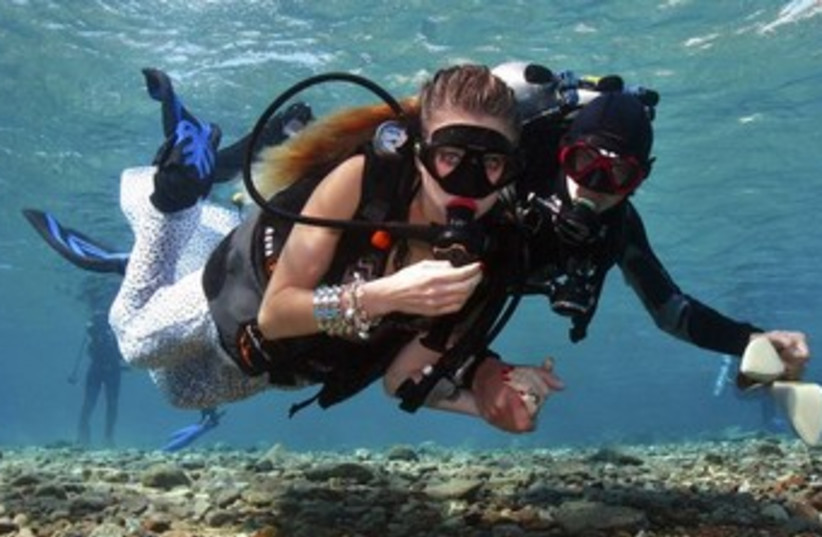 Assistant escorts a model in underwater shoot in Eilat 370 (photo credit: REUTERS)