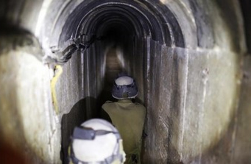 IDF soldiers walk down Hamas terror tunnel 370 (photo credit: REUTERS/Amir Cohen)