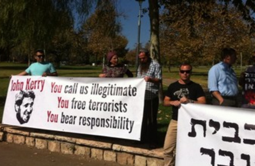 DEMONTSRTERS POSE behind banners Sunday morning  (photo credit: Nadav Malka/YESHA Council)