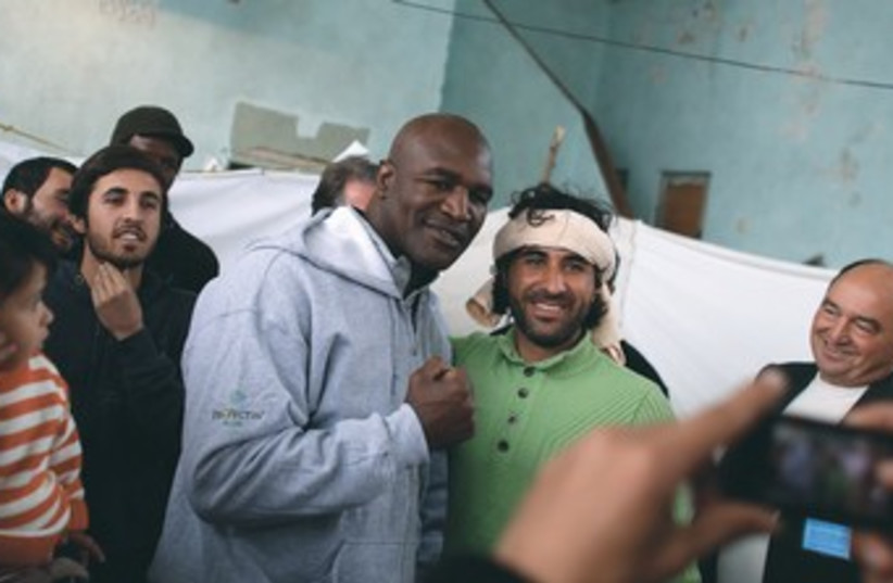 Retired boxer Evander Holyfield with Syrian refugees 370 (photo credit: Stoyan Nenov/Reuters)