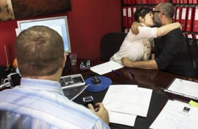 An Israeli couple signs an unofficial marriage agreement 370 (photo credit: REUTERS)