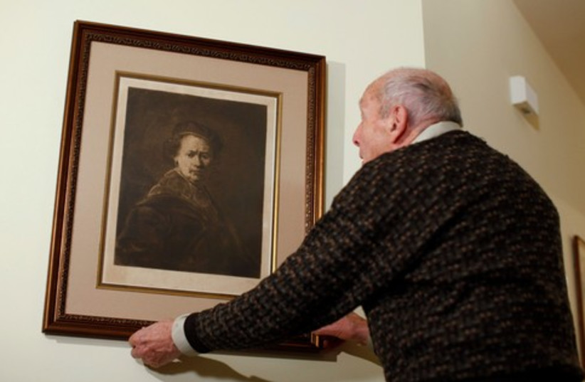 Ettlinger adjusts his print of Rembrandt self-portrait 370 (photo credit: REUTERS)