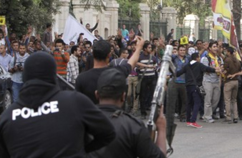 Egyptian police facing pro-Morsi suppoers protest 370 (photo credit: REUTERS/Mohamed Abd El Ghany)