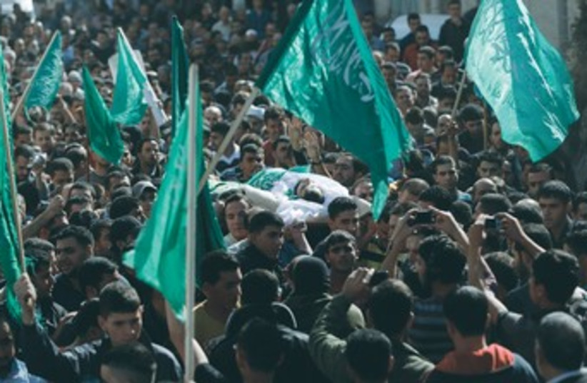 A crowd waves Hamas flags during an Islamist's funeral 370 (photo credit: REUTERS)