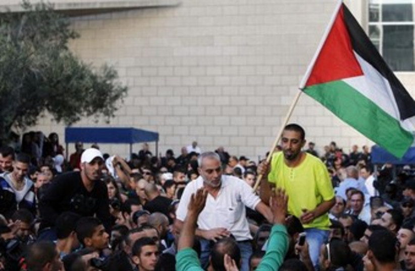 Israeli Arab man raises Palestinian flag 370 (photo credit: REUTERS/Nir Elias)