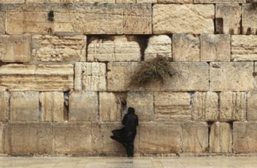 A worshipper braves the weather to pray at the Western Wall