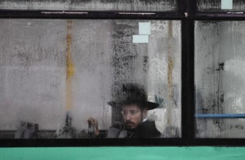 A bus passenger looks out at rain-drenched Jerusalem