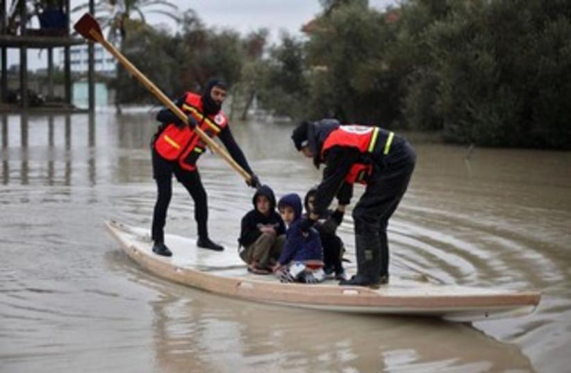 Palestinian civil defense evacuate kids in Gaza 370 (photo credit: REUTERS/Ibraheem Abu Mustafa)