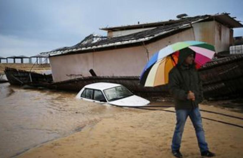 A man walks through flooded Kibbutz Nitzanim 370 (photo credit: REUTERS)
