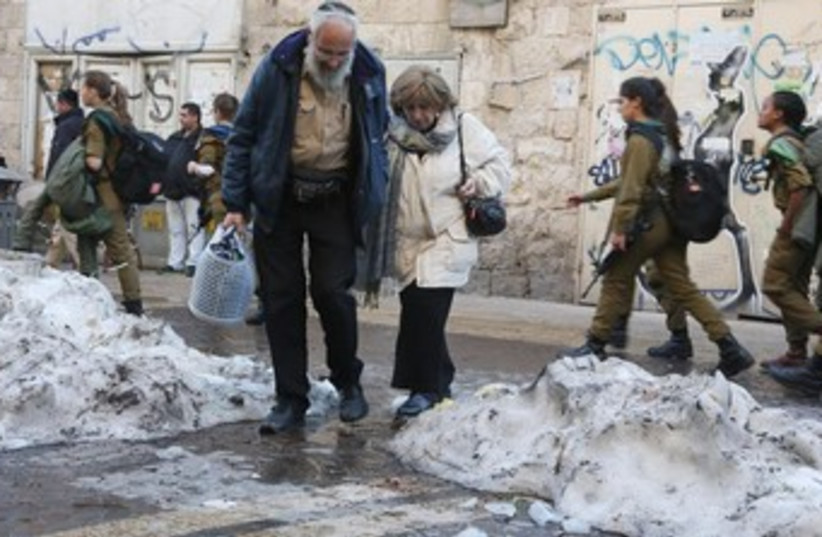 Couple cross road in snowy J'lem 370 (photo credit: Marc Israel Sellem/The Jerusalem Post)