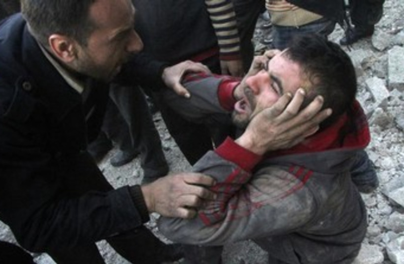A Syrian man reacts after an air raid in Aleppo 370 (photo credit: Reuters)