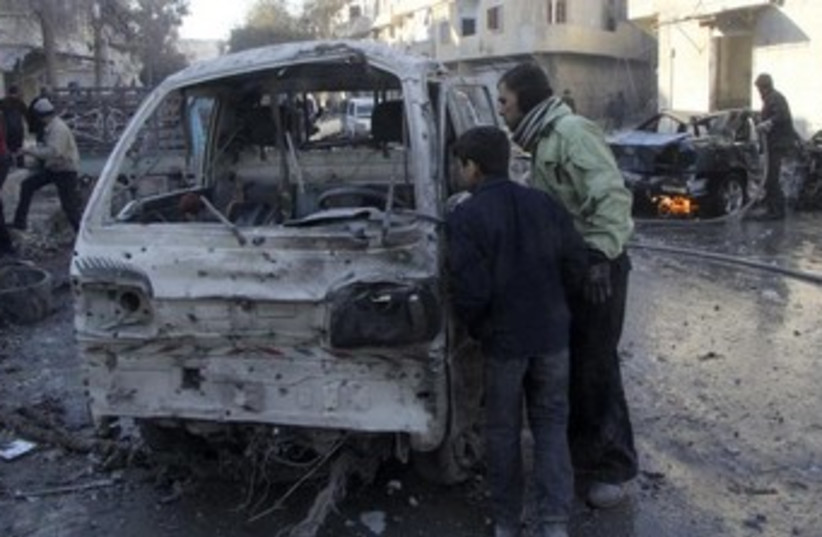 Syrians inspect damaged vehicle after Aleppo airstrike 370 (photo credit: Reuters)