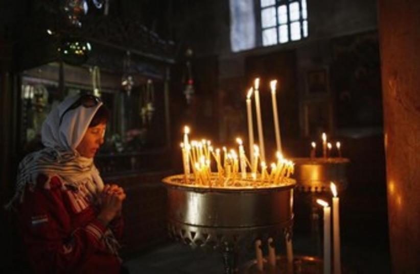 Woman prays at Church of Nativity, Bethlehem. (photo credit: Reuters)