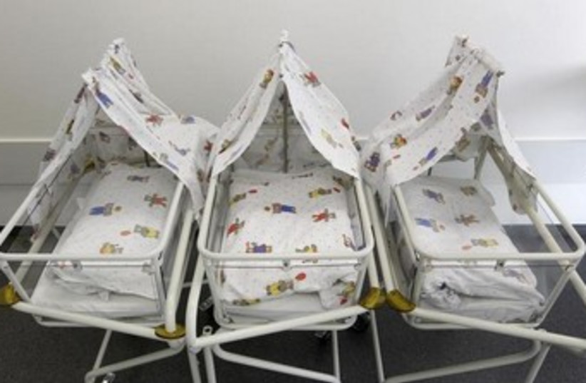 Empty baby cot 370 (photo credit: REUTERS)