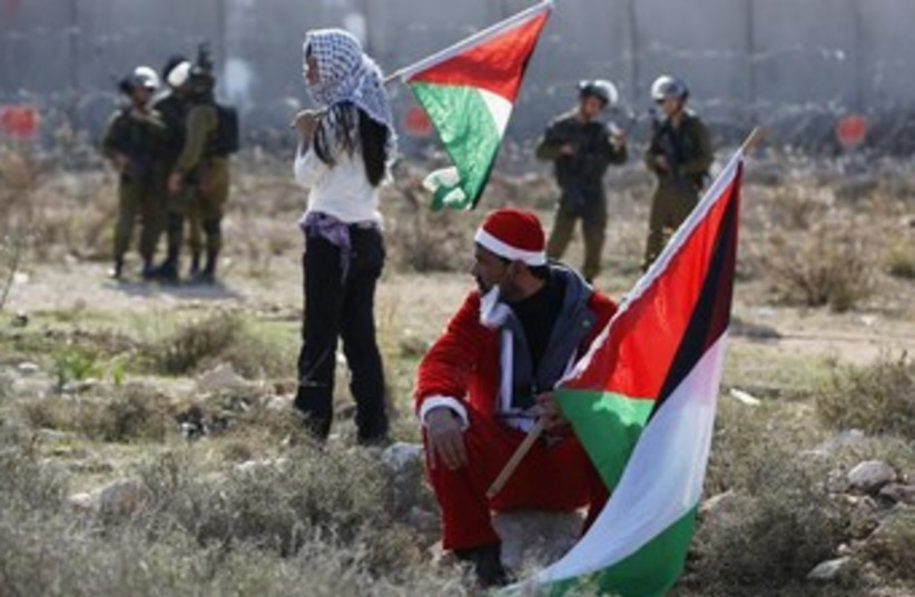 Palestinian protesters in Santa suits in Bilin protests (photo credit: REUTERS/Mohamad Torokman)