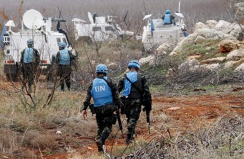 UNIFIL troops inspect remains of shell launched from Lebanon (photo credit: REUTERS/Ali Hashisho)