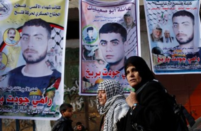 Gaza woman walks past posters of Palestinian prisoners (photo credit: REUTERS/Ibraheem Abu Mustafa)